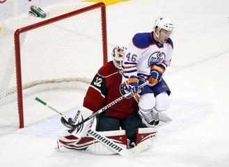 Edmonton Oilers right wing Ryan Keller jumps to avoid a shot on Minnesota Wild goalie Niklas Backstrom