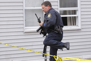 A police officer searches homes for the Boston Marathon bombing suspects in Watertown
