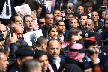 Jordan's Queen Rania holds a picture of recently executed Jordanian pilot Muath al-Kasasbeh during a march after Friday prayers in downtown Amman