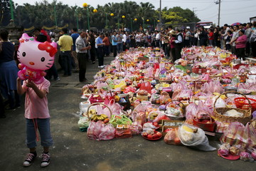A child holds a Hello Kitty balloon as thousands of people surnamed Yeh attend an annual worship ceremony to pay respect to their ancestors on Qingming Festival, also known as Tomb Sweeping Day, in Taoyuan, Taiwan