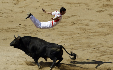 """A """"recortador"""" jumps over a bull during a contest at Pamplona's bullring on the fifth day of the San Fermin festival"""