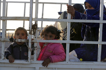 Newly arrived Syrian Kurdish refugees stand at the back of a truck after crossing into Turkey from the Syrian border town Kobani, near the southeastern Turkish town of Suruc