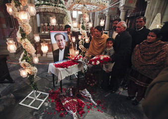 Pakistani Christians place flowers at a portrait of the assassinated Governor of Punjab Taseer after a Sunday service in Lahore