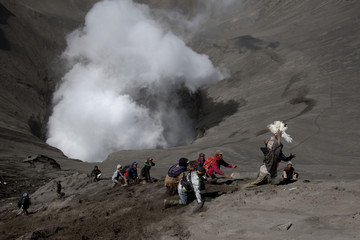 Villagers attempt to catch a chicken thrown by worshippers into a volcanic crater during the annual Kasada festival at Mount Bromo
