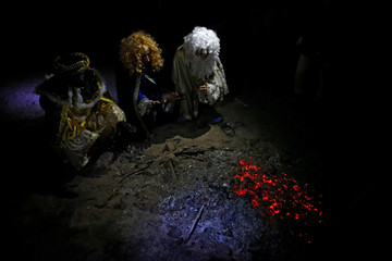 Volunteers of San Carlos Borromeo parish dressed up as the Three Wise Men, warm up next to hot coals after giving away gifts in the shanty town settlement of 'El Gallinero', in the outskirts of Madrid