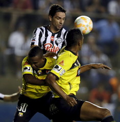 Velazco and Perlaza of Ecuador's Barcelona fights for the ball with Lopez of Paraguay's Libertad during their Copa Libertadores soccer match at the Nicolas Leoz stadium in Asuncion