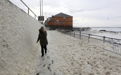 A woman walks through foam, caused by heavy winds and stormy seas, on a coastal path in the town of Portstewart in Northern Ireland