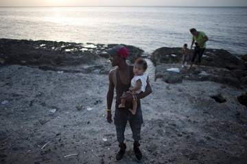 School worker Ivan Gago, 33, holds his 5 months old son as he watches the sunset in Havana