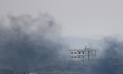 A black flag belonging to the Islamic State is seen through smoke on top of a house in the Syrian town of Kobani, pictured from near the Mursitpinar border crossing on the Turkish-Syrian border in the southeastern town of Suruc