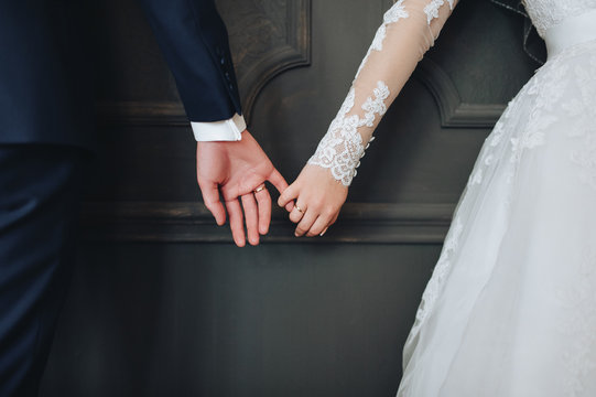 Newlyweds hold hands.
