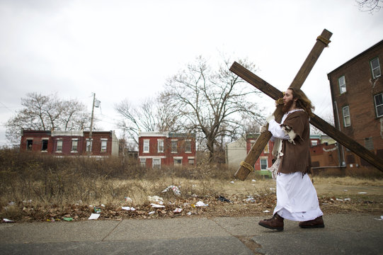 """Michael Grant, 28, """"Philly Jesus,"""" carries a 12 foot cross 8 miles through this blighted area of North Philadelphia towards LOVE Park in Center City as part of a Christmas walk to spread the true message of the holiday in Philadelphia"""