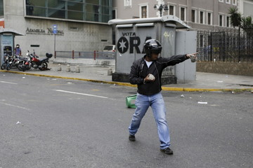 A man holds stones during clashes between supporters of Venezuela's President Maduro and opposition supporters, outside the headquarters of the National Electoral Council (CNE) and the National Assembly in Caracas