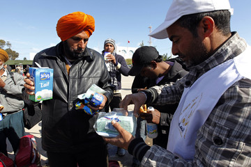 Indians fleeing unrest in Libya receive food and drinks after crossing the border into Tunisia at the border crossing of Ras Jdir