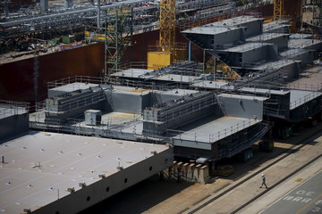 A worker walks past a part of the structure of a ship at Hyundai Heavy Industries' Shipyard in Ulsan