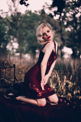 Beautiful and elegant blonde woman with red lips and hair waves wearing wine red nightie posing on the bed outdoors autumn, retro vintage style and fashion.