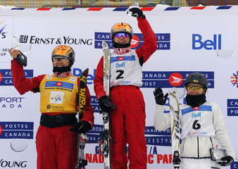 Cheng Shuang of China celebrates her win with teammate Xu Mengtao and Olga Volkova of Ukraine during the Freestyle Ski Aerials World Cup Ladies' finals competition in Calgary