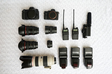 Many different body camera & lenses for SLR cameras lie on a white background image for a business card of a photographer or a photo equipment vendor. Equipment for professional photography