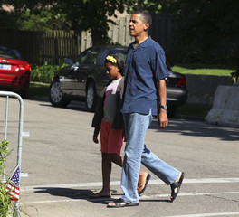 U.S. President Obama and his daughter walk down the street from their home in Chicago