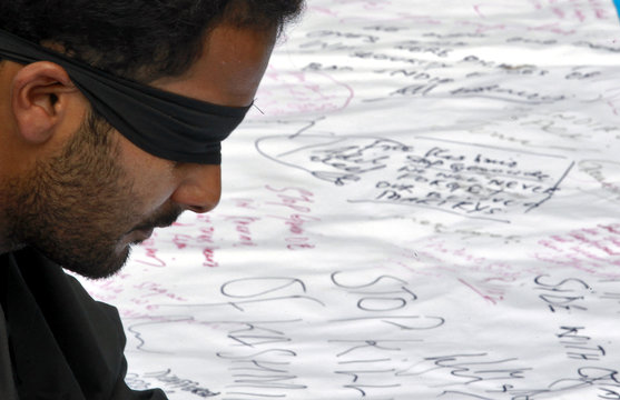 A student sits blindfolded in front of a banner with signatures of people participating in a demonstration in Srinagar