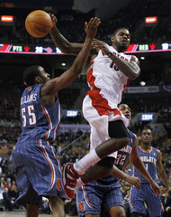 Raptors' Johnson passes the ball beside Bobcats' Williams and Diaw during their NBA basketball game in Toronto