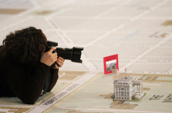 A news photographer takes a picture of a model of White House on a large map that illustrates various routes and access points for upcoming 2013 Inauguration of President Obama at DC Armory in Washington