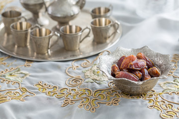 Dates and zam zam water cups on white table cloth