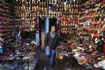 A shopkeeper waits for customers in front of his shoe shop in Kathmandu