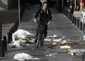 A cyclist rides through garbage on a street in Madrid on the first day of an indefinite street cleaners strike