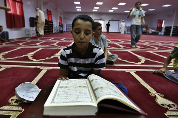 A Syrian refugee boy reads the Koran during Ramadan at the mosque in the Mrajeeb Al Fhood refugee camp
