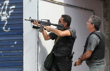 Federal policemen take position during an operation at Grota slum in Rio de Janeiro