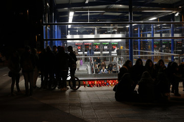 People gather next to candles near a high school attended by two women who were killed in a Halloween party in Madrid