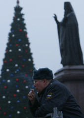 A policeman smokes a cigarette outside an Orthodox church with a traditional festive tree in Rostov-on-Don