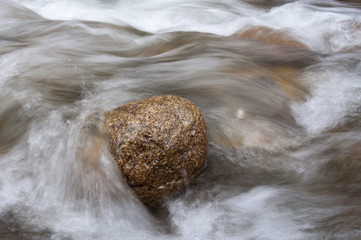 Stone in stream of water of mountain river