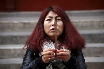 Cheng Liping prays for her husband Ju Kun who was onboard Malaysia Airlines flight MH370 which went missing in 2014, at Lama Temple in Beijing, China