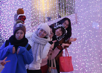 Visitors pose for a picture in front of a light installation for Christmas celebrations in Beijing