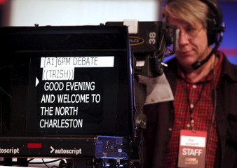 Fox Business News cameraman Joe Schmitt lines up his camera as crew members prepare the stage for Thursday's Fox Business News Republican Presidential Debate at the North Charleston Coliseum in North Charleston