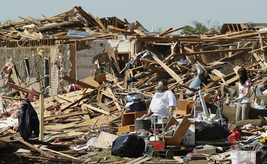 A woman wearing a respirator rests in the rubble of a tornado-destroyed home in Oklahoma City