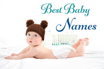 Cute baby wearing funny cap on bed