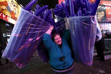 A woman carries balloons during New Year celebrations in Times Square in the Manhattan borough of New York.
