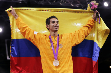 Bronze medallist Colombia's Oscar Munoz Oviedo poses with his national flag at the men's -58kg taekwondo victory ceremony during the London 2012 Olympic Games at the ExCeL arena
