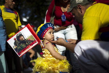 A little girl, wearing the colors of the Venezuelan flag and carrying a picture of Venezuelan President Hugo Chavez, takes part in a gathering at Plaza Bolivar in Caracas