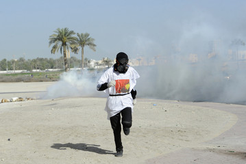 A protester runs to take cover from tear gas fired by riot police during early hours of clashes in the village of Sanabis, west of Manama