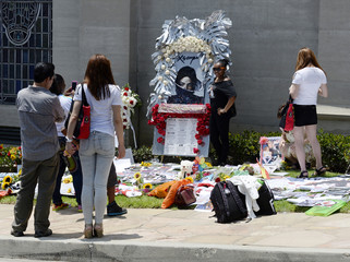 Fans get their picture take in front of flowers and signs outside the mausoleum where Jackson is interred at Forest Lawn Memorial Park-Glendale