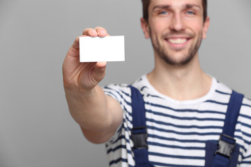 Handsome worker with business card on grey background, closeup