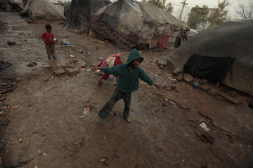 Children play in the rain near their families' makeshift tents at a slum on the outskirts of Islamabad