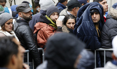 Migrants queue at the compound outside the Berlin Office of Health and Social Affairs waiting to register in Berlin