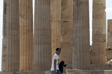 A man walks in front of the temple of the Parthenon at the archaeological site of the Acropolis in Athens