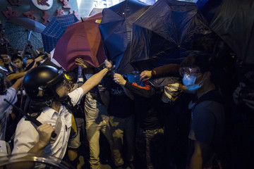 A riot policeman takes an umbrella from a pro democracy protester during a scuffle on a blocked road at Mongkok shopping district in Hong Kong