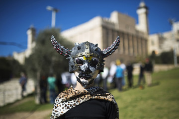 A Jewish settler youth is dressed in a costume, as the Tomb of the Patriarchs is seen in the background, during a parade marking Purim in Hebron