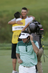 Watson of U.S. walks off the green as Kaymer of Germany celebrates with his caddy after winning the 92nd PGA Golf Championship